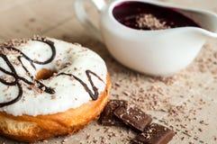 De doughnut met jam gaf witte chocolade water Donkere chocolade, melk Stock Foto's