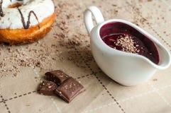 De doughnut met jam gaf witte chocolade water Donkere chocolade, melkcho Stock Afbeeldingen