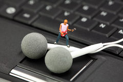 De downloadconcept van de muziek. Miniatuur gitaarspeler. Stock Fotografie