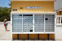 De dozen die van de postkantoorpost een muur buiten en vrouw voeren Echte coptijo van Gr spanje Stock Foto's