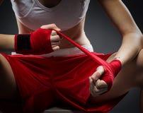 De in dozen doende vrouw bindt het verband op zijn hand, alvorens op te leiden Stock Afbeeldingen