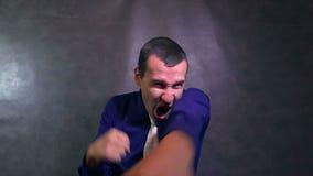De in dozen doende zakenman die van de strijdenmens zijn wapens boze langzame motie golven stock video