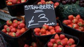 De dozen van aardbeien verkopen in de markt stock afbeelding