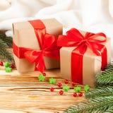 De dozen van de ambachtgift met rode lint en boog, groene Kerstboom, decoratie, witte plaid op houten achtergrond Kerstmis en Nie royalty-vrije stock afbeelding