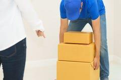De dozen van de bezorgerholding in klantenhuis die - packag ontvangen stock afbeeldingen