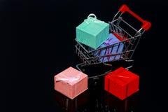 De dozen van de gift in geïsoleerdm boodschappenwagentje Stock Foto