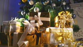 De dozen van de luxegift onder Kerstboom, de decoratie van het Nieuwjaarhuis, het gouden verpakken van Kerstman stelt, feestelijk stock video