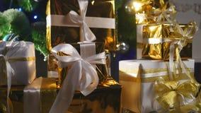 De dozen van de luxegift onder Kerstboom, de decoratie van het Nieuwjaarhuis, het gouden verpakken van Kerstman stelt, feestelijk stock footage