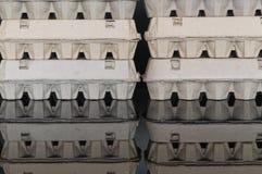 De dozen van het kartonei op een zwarte weerspiegelende oppervlakte Stock Fotografie