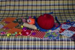De draad, stof, knopen, naald voor het naaien Stock Afbeeldingen