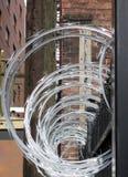 De draad van het concertinascheermes tegen bakstenen muur Stock Afbeelding