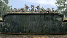 De draakbeeldhouwwerken op de bakstenen muur van Buu Thanh die omringt begraven van Keizer Turkije Duc in Turkije Duc Royal Tomb  stock foto