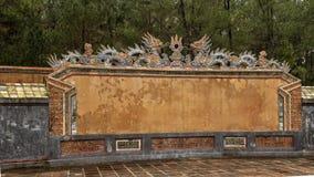 De draakbeeldhouwwerken op de bakstenen muur van Buu Thanh die omringt begraven van Keizer Turkije Duc in Turkije Duc Royal Tomb  stock fotografie