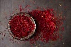 De draden en het poeder van het saffraankruid in uitstekende ijzerschotel stock foto's