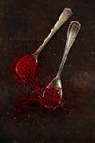 De draden en het poeder van het saffraankruid in uitstekende oude lepels royalty-vrije stock fotografie