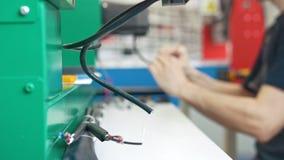 De draden van machinesmateriaal vooraan elektricien op overall werkt met energiepaneel en machinesmateriaal stock footage
