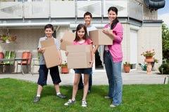 De dragende dozen van de familie in nieuw huis Royalty-vrije Stock Afbeelding