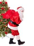 De dragende zak van de Kerstman door Kerstmisboom. Royalty-vrije Stock Fotografie
