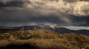 De dramatische vorm van de regenonweerswolk over de sneeuwberg stock afbeeldingen