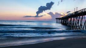 De dramatische zonsopgang steekt omhoog het wolken en pastelkleurenlicht aan omhoog de wolken Een oude houten oceaanpijler bij zo royalty-vrije stock foto's