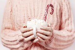 De drank van het Kerstmisnieuwjaar, witte mok met heemst in wijfje dient gebreid roze sweater en Suikergoedriet in Traditionele d stock fotografie