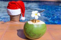 De drank van het kokosnotensap met de Kerstmanhoed van mensenkerstmis Royalty-vrije Stock Foto's