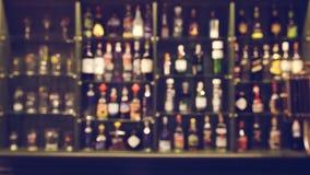 De drankfles van de onduidelijk beeldalcohol op barteller in de donkere nacht backg Stock Afbeelding