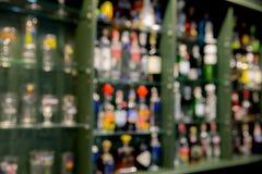 De drankfles van de onduidelijk beeldalcohol op barteller in de donkere nacht backg Stock Foto's