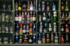 De drankfles van de onduidelijk beeldalcohol op barteller in de donkere nacht backg Royalty-vrije Stock Afbeelding