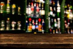De drankfles van de onduidelijk beeldalcohol op barteller in de donkere nacht backg Royalty-vrije Stock Foto