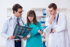 De drie artsen die aftastenresultaten van x-ray beeld bespreken stock fotografie