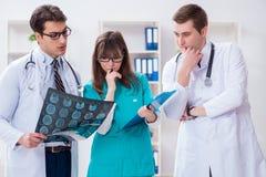 De drie artsen die aftastenresultaten van x-ray beeld bespreken royalty-vrije stock afbeeldingen