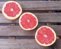 De drie grapefruithelften op een houten achtergrond Stock Foto
