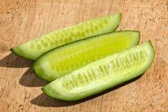 De drie helften van komkommer op houten scherpe raad Stock Foto