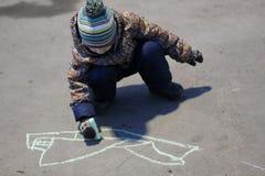 De drie-jaar-oude jongen in gekleurde bovenkleding en hoed trekt krijt op het asfalt in de vroege lente stock fotografie