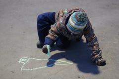 De drie-jaar-oude jongen in straatkleren en een hoed trekt met krijt op de bestrating in de vroege lente royalty-vrije stock foto's