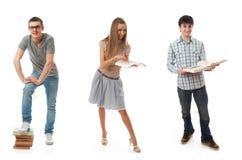 De drie jonge studenten die op een wit worden geïsoleerde Stock Afbeelding