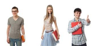 De drie jonge studenten die op een wit worden geïsoleerdg Royalty-vrije Stock Afbeeldingen