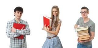 De drie jonge studenten die op een wit worden geïsoleerdA Stock Afbeeldingen