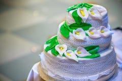 De drie-tiered huwelijkscake is verfraaid met bloemen en bevindt zich op de lijst naast een plaat en een bestek Stock Foto's