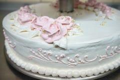 De drie-tiered huwelijkscake is verfraaid met bloemen en bevindt zich op de lijst naast een plaat en een bestek Stock Foto