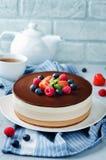 De drievoudige die cake van de chocolademousse met verse bessen wordt verfraaid Stock Afbeeldingen