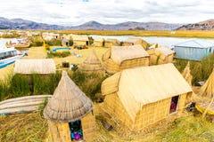 De drijvende Eilanden op Meer Titicaca Puno, Peru, Zuid-Amerika, met stro bedekten huis. Dichte wortel die Khili plant royalty-vrije stock afbeelding