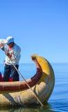 DE DRIJVENDE EILANDEN VAN UROS, PUNO, PERU 31 MEI, 2013: Niet geïdentificeerde inheemse mens in een traditionele boot op Titicaca stock foto's