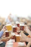 De drinkers van het Oktoberfestbier heffen glas op royalty-vrije stock afbeeldingen
