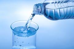 De drinkwaterfles en het gietende water in glas op samenvatting vertroebelden lichtblauwe achtergrond stock fotografie