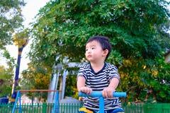 De droevige Aziatische raad van het jong geitje berijdende geschommel bij de speelplaats onder sunlig Royalty-vrije Stock Fotografie