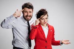 De droevige bedrijfsman en de vrouw die op een grijze achtergrond strijdig zijn Royalty-vrije Stock Afbeelding