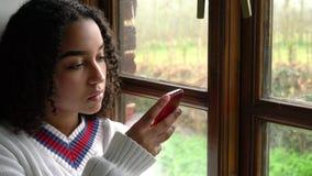 De droevige biracial Afrikaanse Amerikaanse jonge vrouw die van de meisjestiener haar mobiele celtelefoon of smartphone voor soci stock footage
