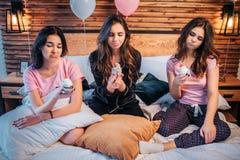 De droevige en verstoorde jonge vrouwen zitten op bed in ruimte Zij houden cakes en bekijken hen De jonge vrouwen zijn ongelukkig stock afbeeldingen